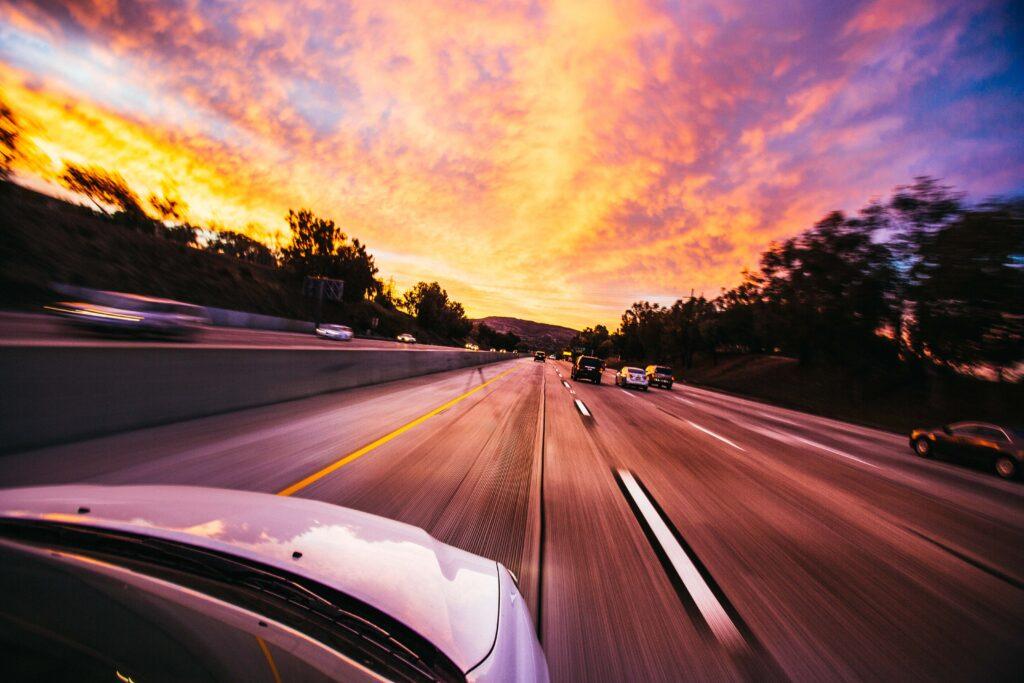 DIY car sound deadening white car cruising highway sunset