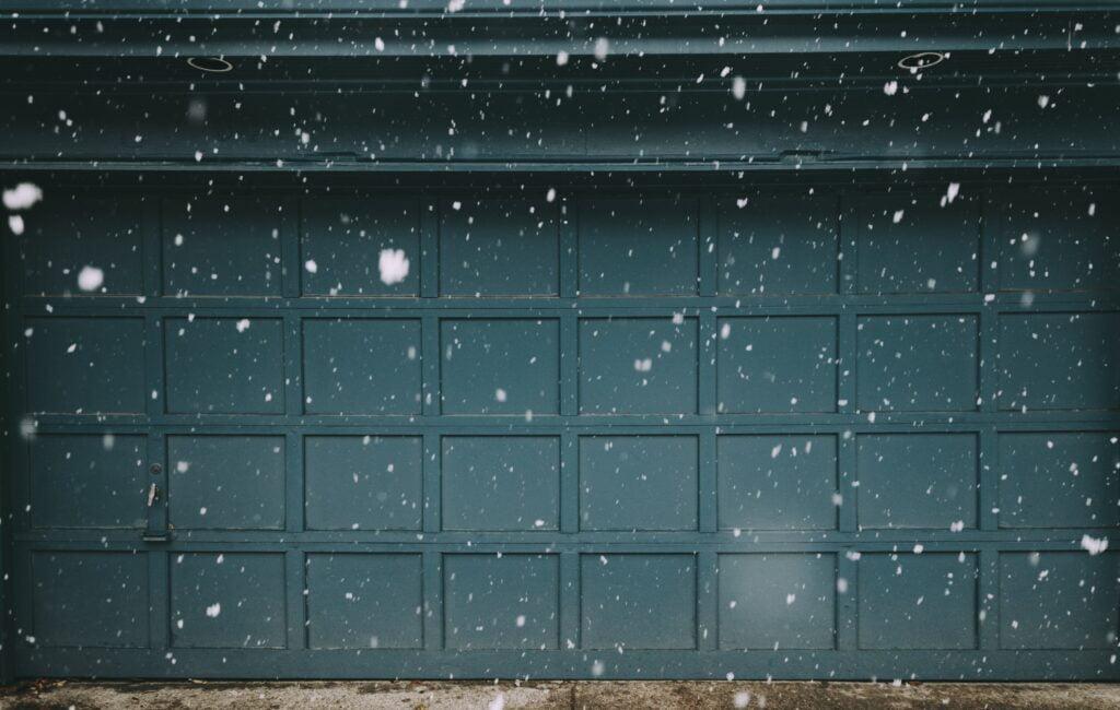 seal garage door gaps green garage door closed snow falling outside